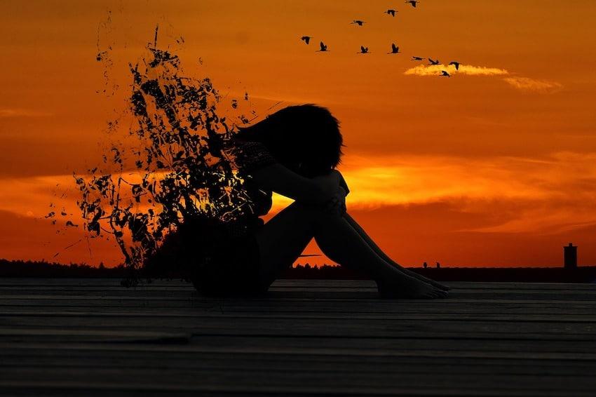 Frau in gekrümter Haltung macht sich sorgen -Die Kraft Deiner Gedanken, in Sorge bleiben