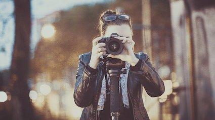 Fotografin mit Kamera - Verfeinere Deinen Fokus